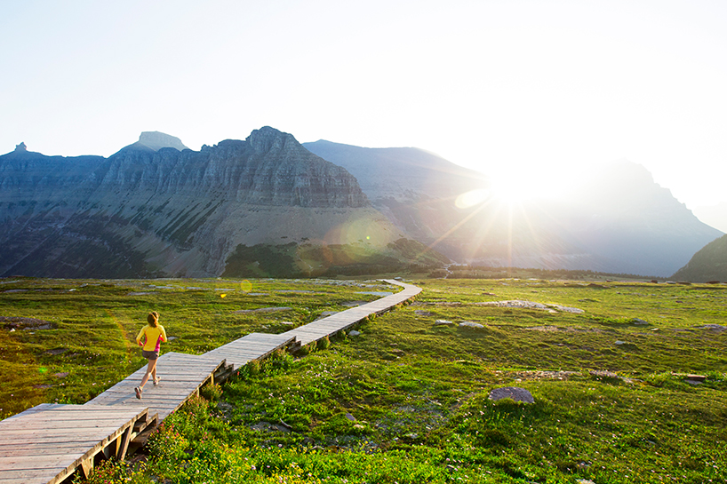 Photo of a person running on a wooden road towards a mountain in the background