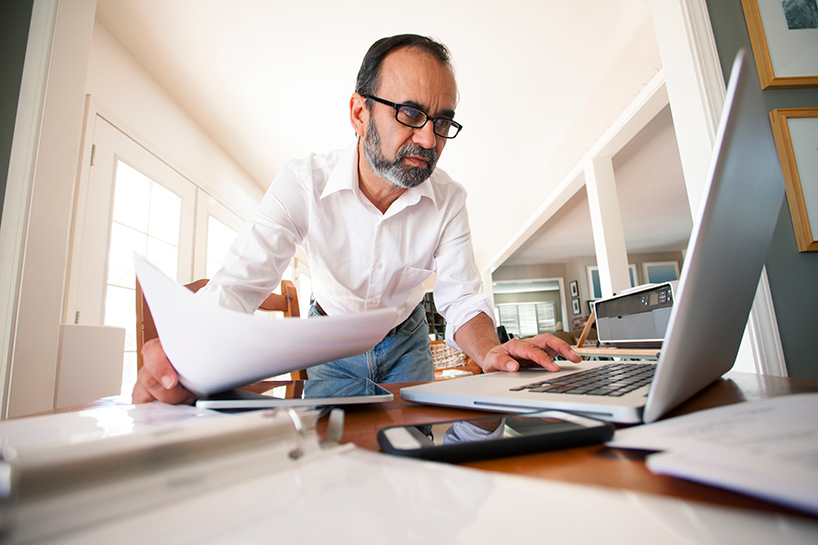 Photo of a man leaning over a desk in his home office. He is holding documents with one hand and typing on a laptop with the other hand.