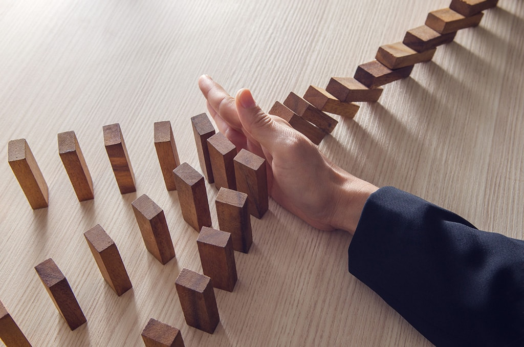 a hand blocking rows of dominoes from falling