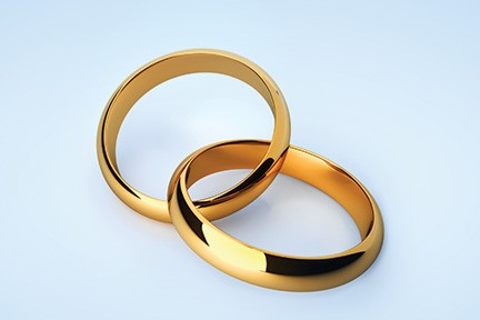 2 gold rings arranged so that they form a heart symbol