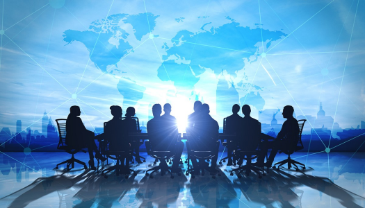 workforce around a conference table with global imagery as a backdrop