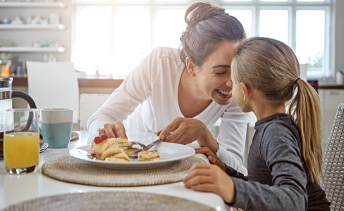 Mother and daughter having breakfast in a kitchen