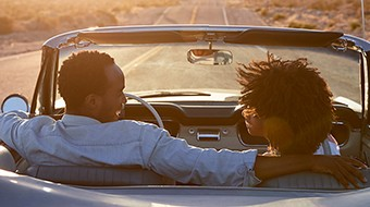 Rear view of a young couple driving at sunset