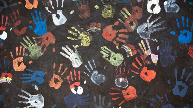 Black canvas with multicolored hand prints.