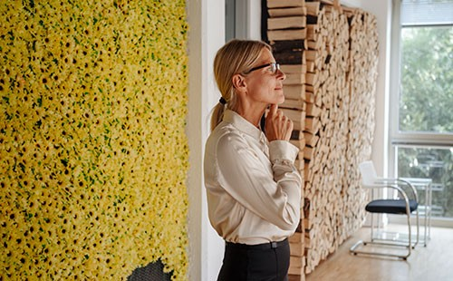 Businesswoman in office at wall with sunflowers thinking