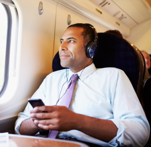Man listening to podcast on train.