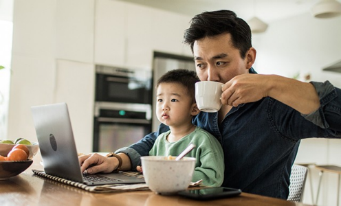 Photo of a father sitting with his son in his lap at the kitchen table. The father is holding a cup of coffee and typing on a laptop.