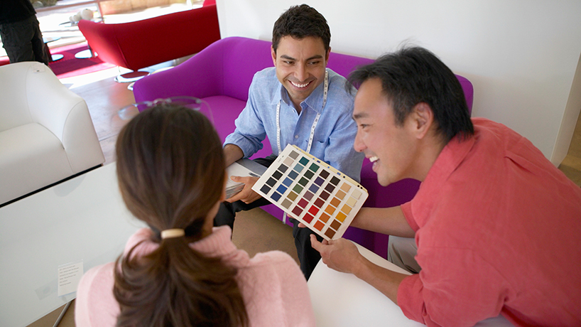 Salesman helping a couple select furniture fabric.