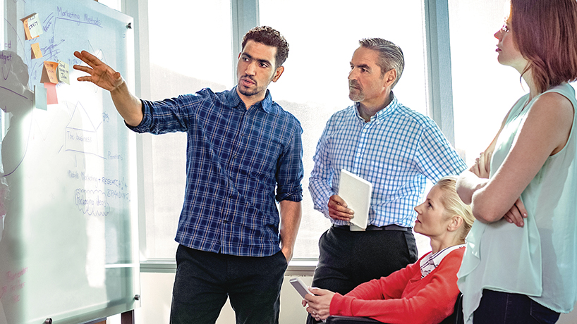 Group of professionals looking at a whiteboard