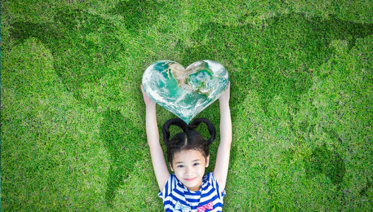 Young girl laying on a map of the world made from grass while holding a heart  containing a satelite view of planet earth